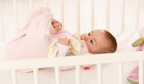 малыш в деревянной кроватке