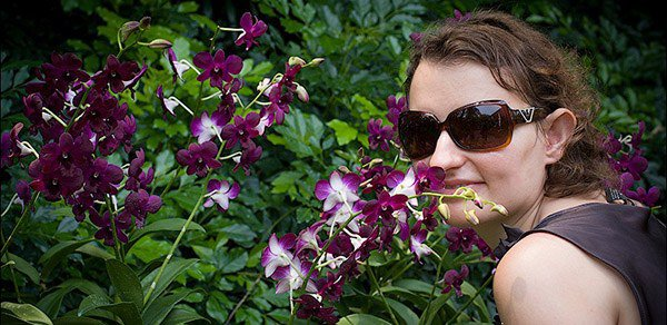 женщина нюхает орхидею