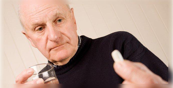 Пожилой человек пьет таблетку